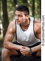 Serious well built man sitting in the park - Strong and...