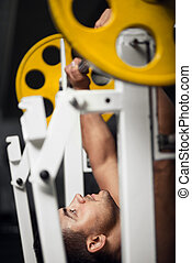 Strong male weightlifter lifting a barbell - Exerting...