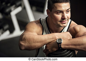 Positive well built man leaning on a dumbbell - Pleasant...
