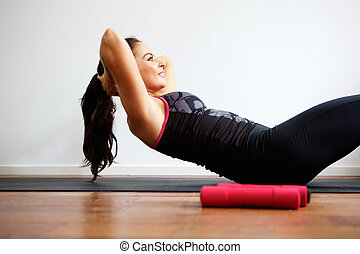 Woman doing sit up on yoga mat - Side portrait of woman...