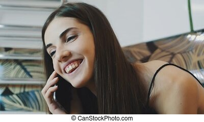Portrait of brunette young girl talking on phone in...