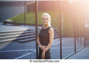 Mature busineswoman standing in front of building - Portait...