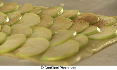 View of chef rolls dough with sliced apple - View of cook...