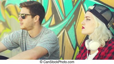 Trendy young hipster couple sitting in the street relaxing...