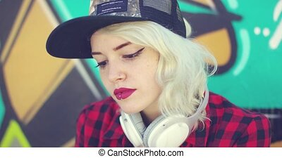 Gorgeous hipster young blond woman browsing her mobile for...