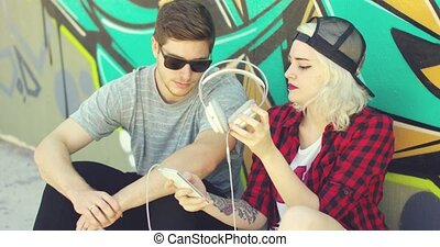 Fun young hipster couple listening to music on a mobile...