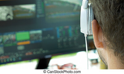 Video broadcast editor with headphones at screen - Video...