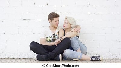 Trendy hipster young couple in love relaxing on a sidewalk...