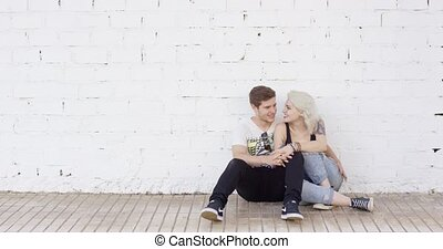 Loving young urban couple sitting in a close embrace on a...