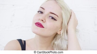 Attractive blond woman with a lip piercing wearing red...