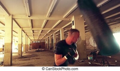 Strong athlete hits a punching bag. Medium shot. - Strong...