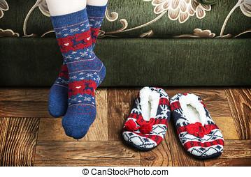 Christmas female legs in socks and slippers. vignette for...