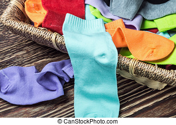 scattered multi-colored socks and laundry basket on a wooden...