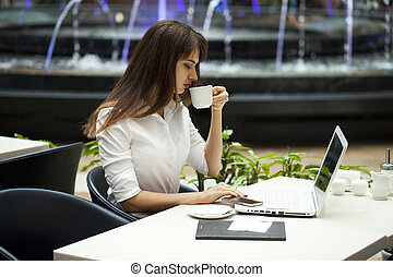 Young beautiful business woman drinking coffee