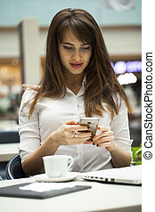 Young beautiful business woman reading messages