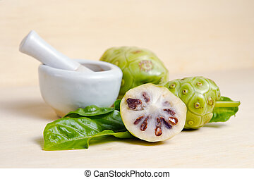 Exotic Noni fruit and leaf isolated on wood board - Noni...