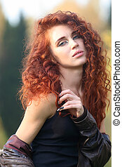 Beautiful woman with red hair in leather jacket poses in forest, shallow dof