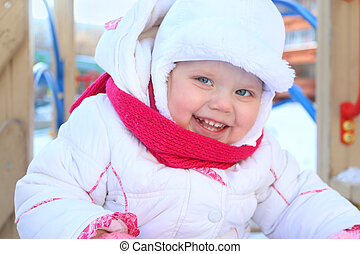 Happy little girl in white plays on playground and smiles at winter sunny day