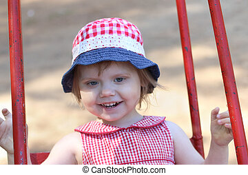 Little happy girl in hat swings on children playground at...