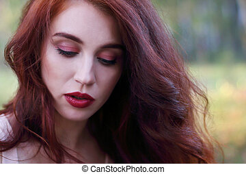 Woman with red hair looks down in autumn forest, shallow dof, close up