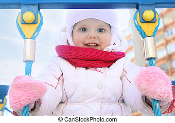 Little girl in white plays on playground and smiles at winter sunny day