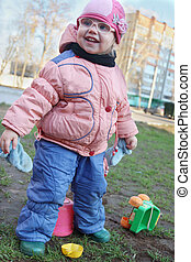 Happy little girl in fake glasses plays with plastic toys outdoor
