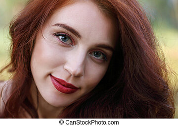 Woman with red hair smiles in forest, shallow dof, close up