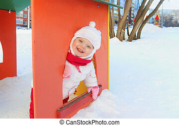 Happy little girl plays in bright small house on playground at winter sunny day