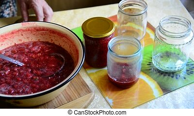 Woman puts handmade Strawberry jam in jar - Woman puts...