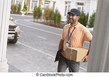 Young man making home delivery - Careful delivery. Smiling...