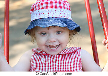 Little girl in hat swings on children playground and smiles...
