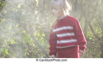 Girl child extinguish fire - Girl in refugee dense smoke...