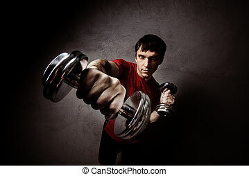 Muscle man posing with dumbbell s on wall backdrop