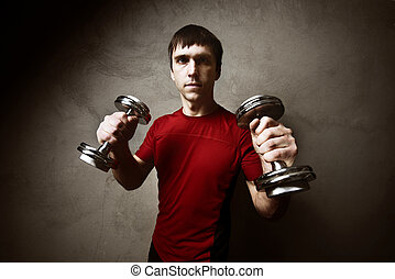 Muscle man posing with dumbbells on the wall backdrop