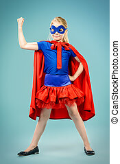 strong girl - Little girl playing in superhero. Studio shot.