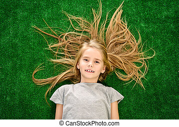 restless child - Funny little girl lying on a green lawn and...