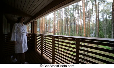 young girl goes to the balcony in white Bathrobe in the...