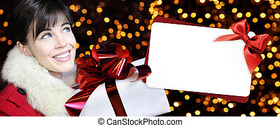woman with christmas box and gift card in golden lights background