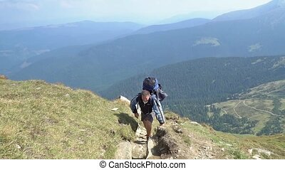 Bearded man climbs the mountain, cl - Bearded man with a...