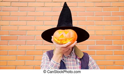 Young man with Jack latern pumpkin - Young man wearing witch...