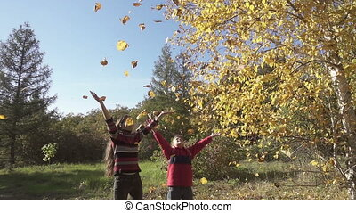 Two kids throwing up the autumn leaves, slow motion - Two...