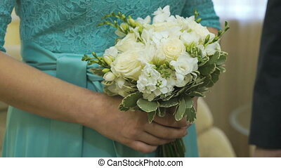 Bride holding a wedding bouquet in a wedding hall -...