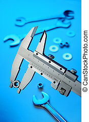 Vernier caliper measuring steel nut with different metal...