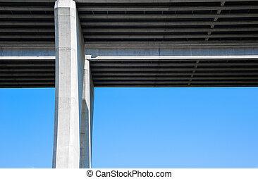 Underside of concrete bridge and pylon on sky.