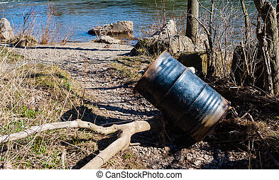 Metal drum lying at angle near river.