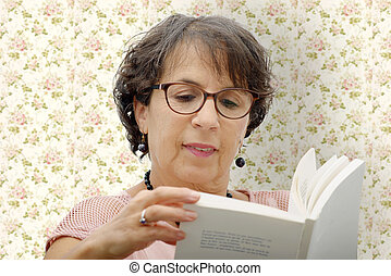 mature brunette woman reading a book - a mature brunette...
