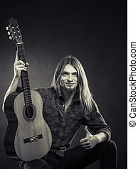 Young man holding guitar. - Young stylish man long haired...