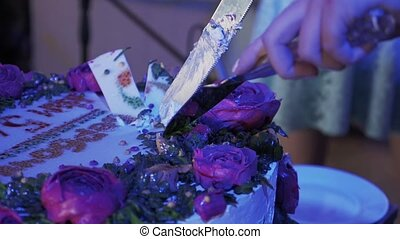 Woman cut huge cake with roses by two knives at celebration event. Purple light