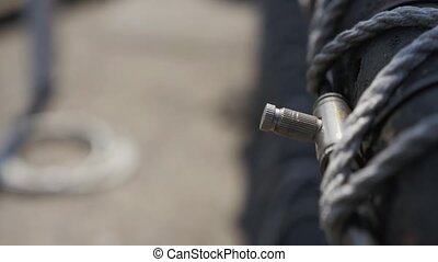 Water spray from metal valve on black fence. Summer sunny day. Pipe