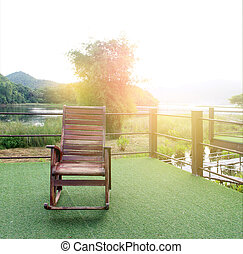wooden rocking chair on green grass in the garden with burst...